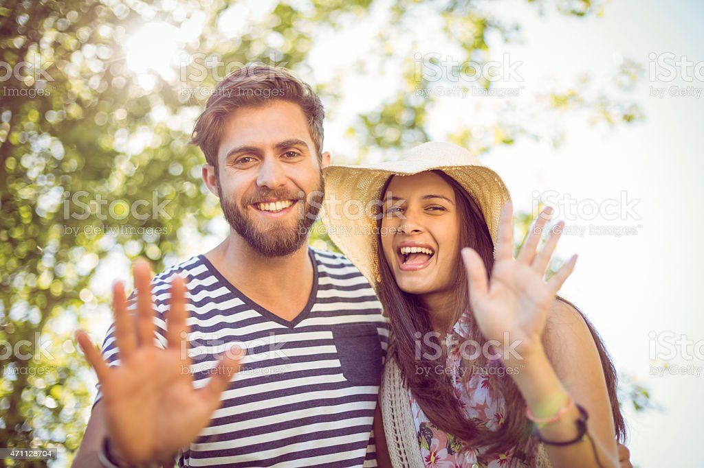 Couple waving at the camera outdoors in the sunlight stock photo