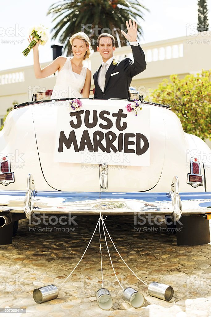 Couple Waving In Car With Cans Attached To It stock photo