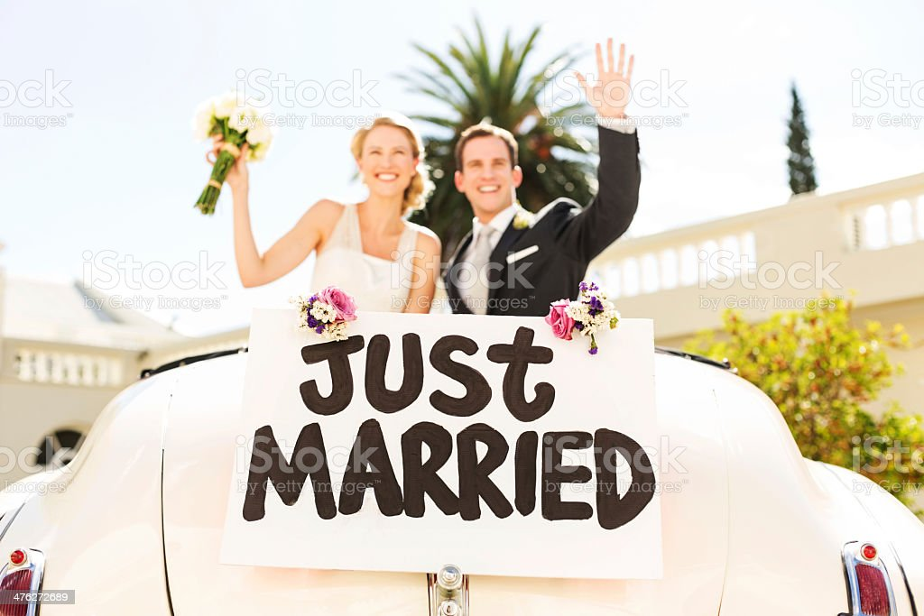 Couple Waving With Just Married Sign Attached Car stock photo