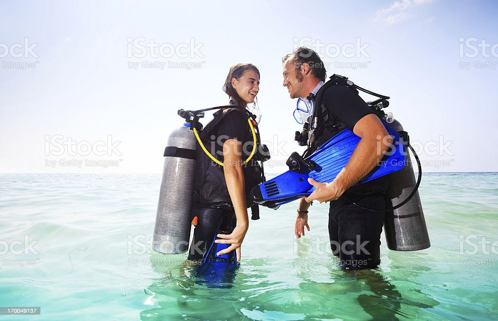 Couple wearing diving equipment in the water. stock photo