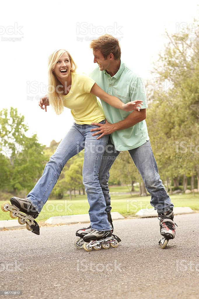 Couple Wearing In-Line Skates In Park stock photo