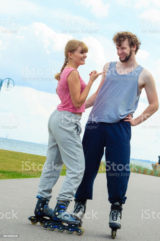 Couple wearing rollerskates looking at each other stock photo