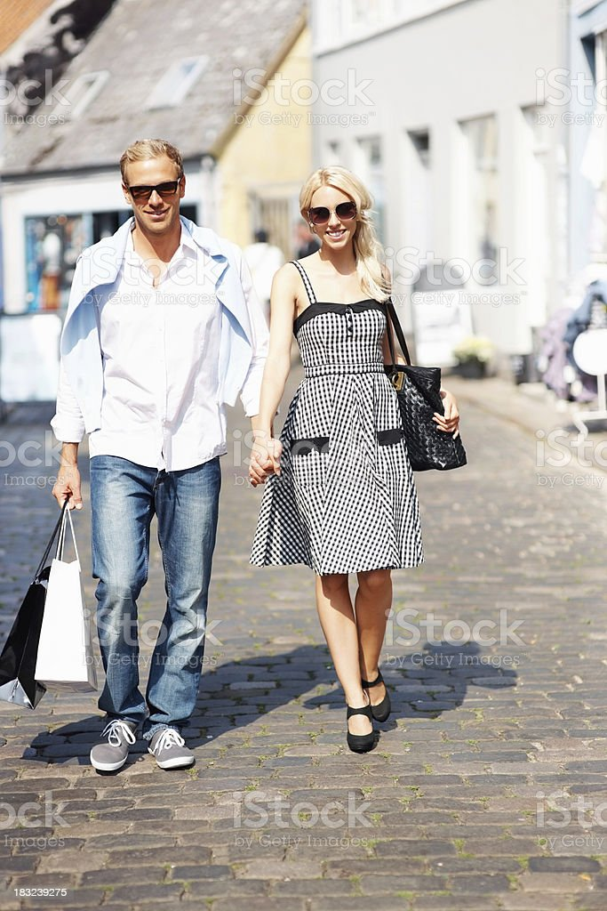 Couple wearing sunglasses while walking with shopping bags royalty-free stock photo
