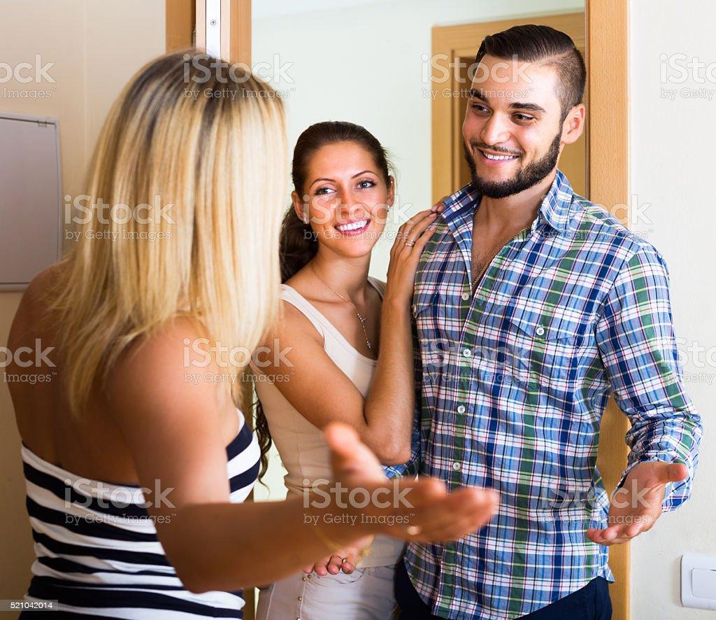 Couple welcoming friend at doorway stock photo
