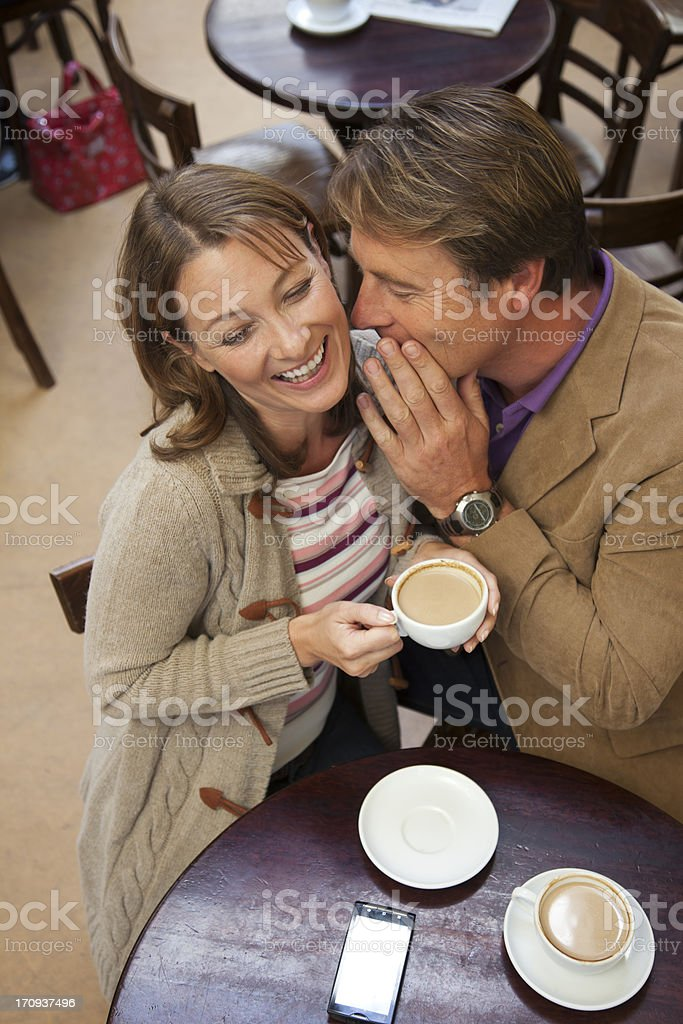 Couple Whispering While Having Coffee royalty-free stock photo