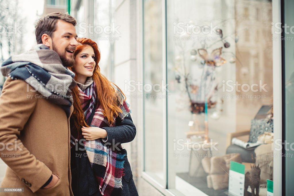 Couple window shopping outdoors in winter city street. stock photo