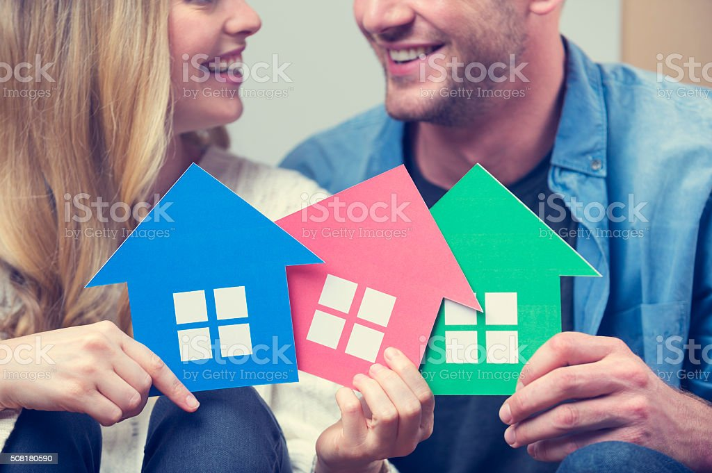 Couple with 3 house symbols – choice concept. stock photo