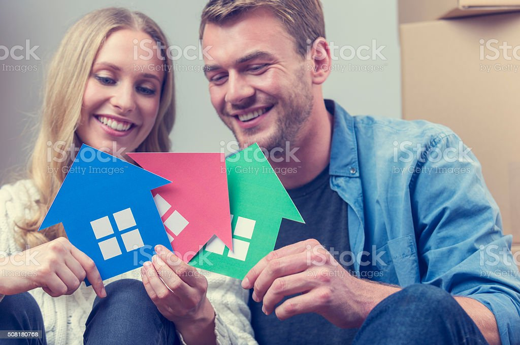 Couple with 3 house symbols. choice concept. stock photo