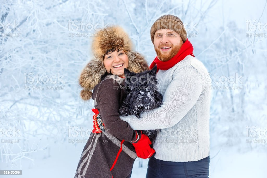 couple with a dog in winter stock photo