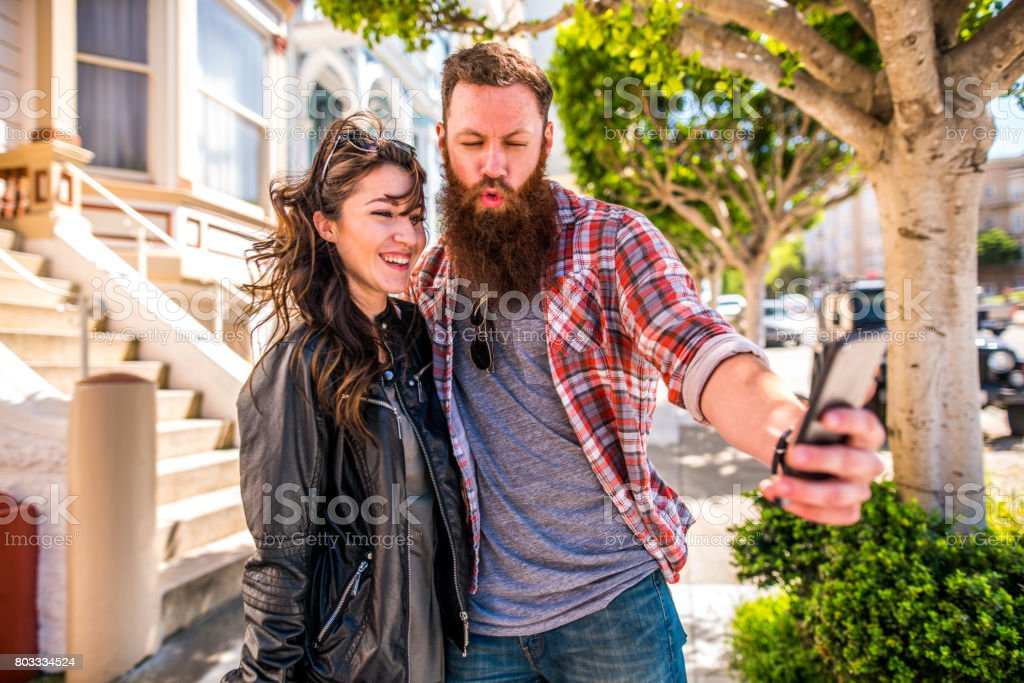 A couple with a dog on a city walk stock photo
