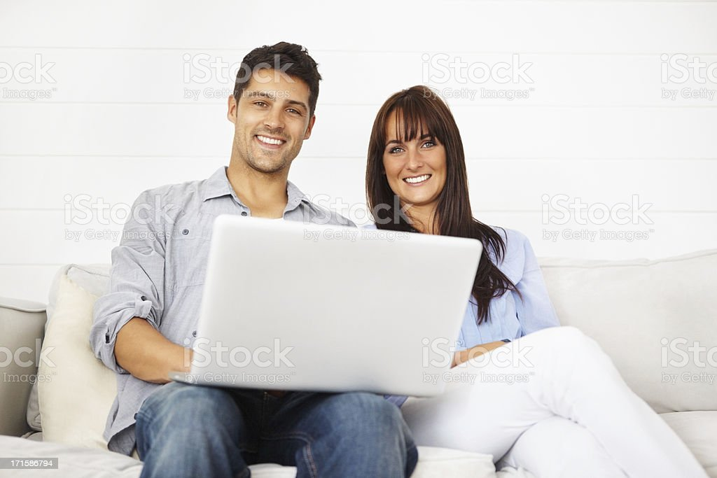 Couple with a laptop sitting on the sofa royalty-free stock photo