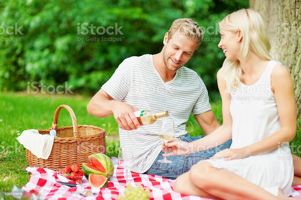 Couple with a man pouring champagne in glass on picnic royalty-free stock photo