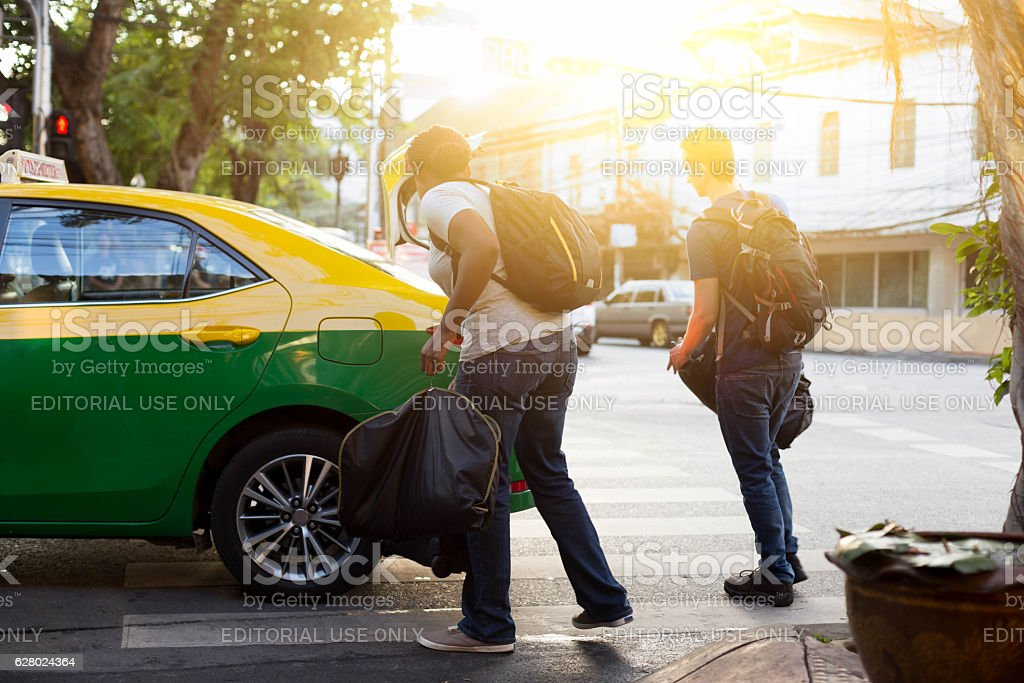 couple with a travel bag getting in a taxi vacation stock photo