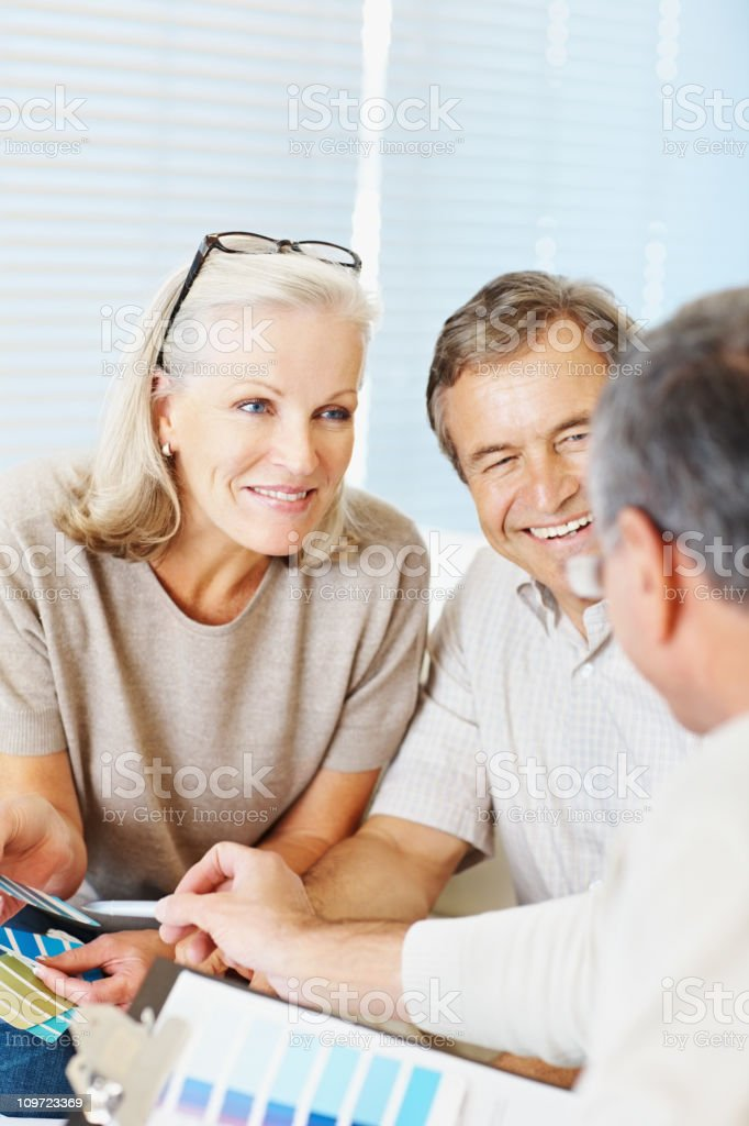 Couple with an interior decorator deciding on color schemes stock photo