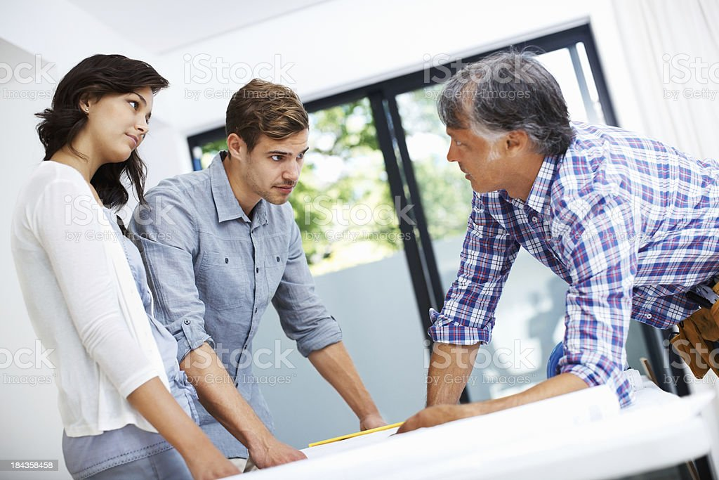 Couple with architect discussing home plan royalty-free stock photo