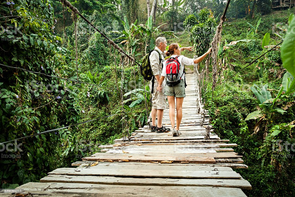 Couple with backpack hiking in rainforest stock photo