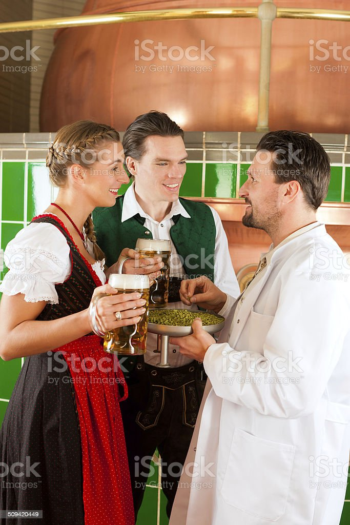 Couple with beer and their brewer in brewery stock photo