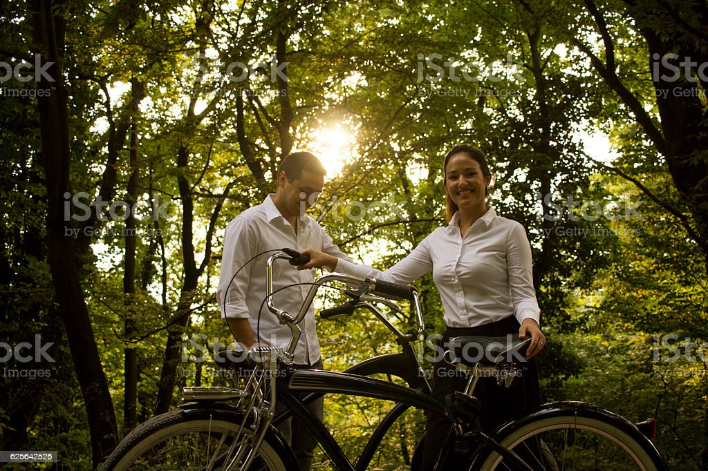 Couple with bicycles in a forest, sun flare stock photo