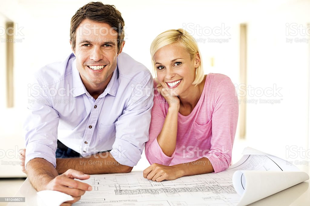 Portrait of happy mid adult couple with blueprint leaning on table at...