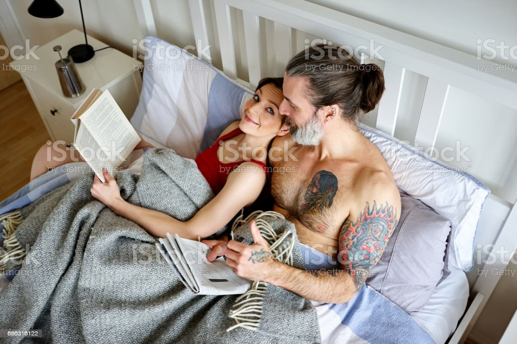 Couple with book and newspaper in bed stock photo