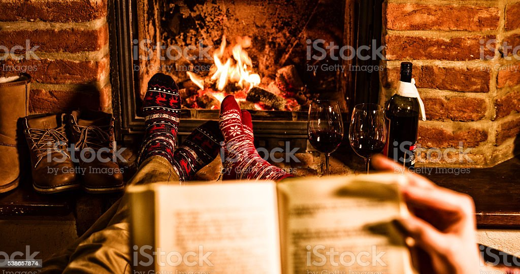 Couple with book resting by fireplace during Xmas stock photo