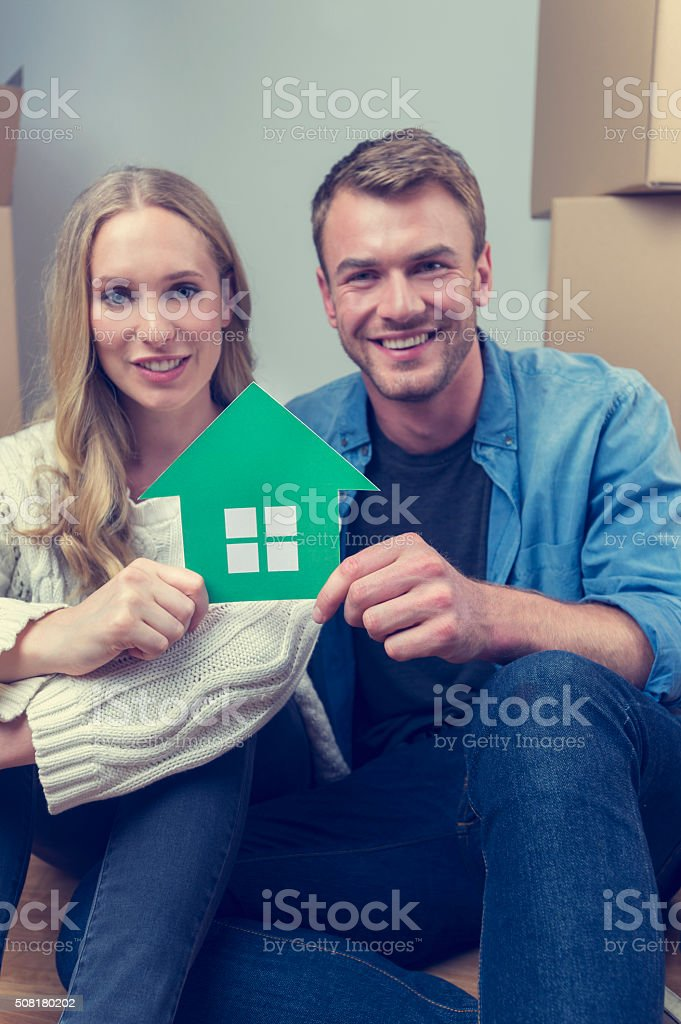 Couple with cardboard moving boxes and house symbol stock photo