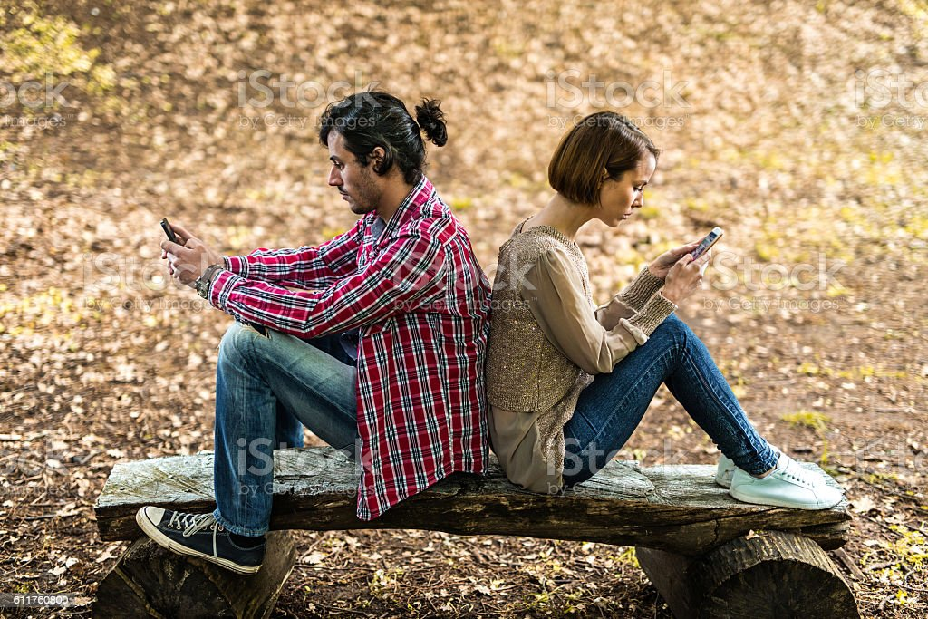 Couple with cell phones sitting back to back at park. stock photo