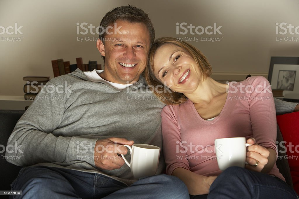 Couple With Coffee Mugs Watching Television royalty-free stock photo