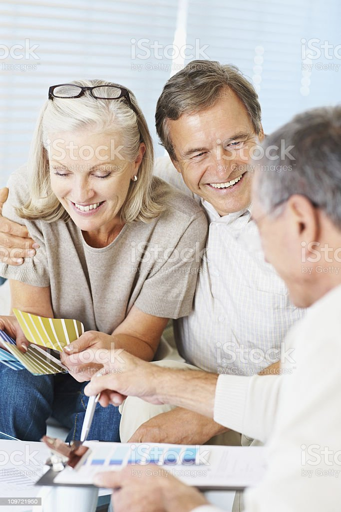 Couple with decorator choosing color royalty-free stock photo