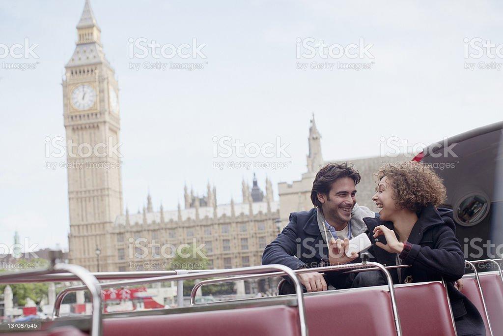 Couple with digital camera riding double decker bus near Big Ben clocktower in London stock photo