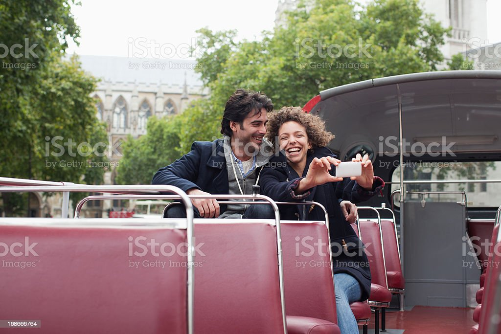 Couple with digital camera riding double decker bus near Big Ben clocktower in London royalty-free stock photo