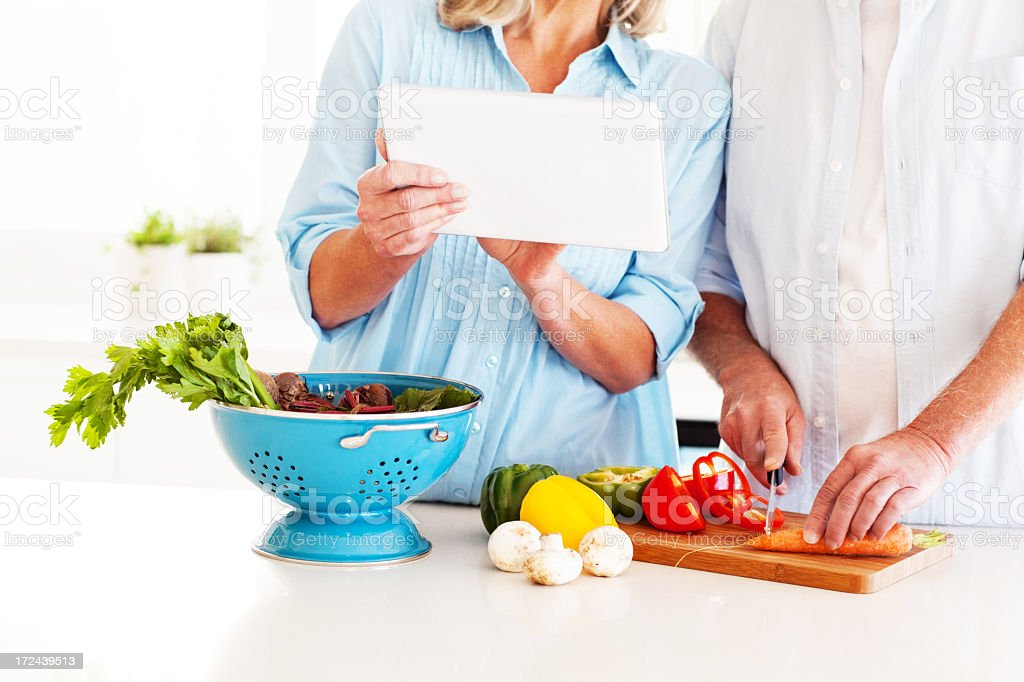 Couple With Digital Computer Cutting Vegetables In Kitchen royalty-free stock photo