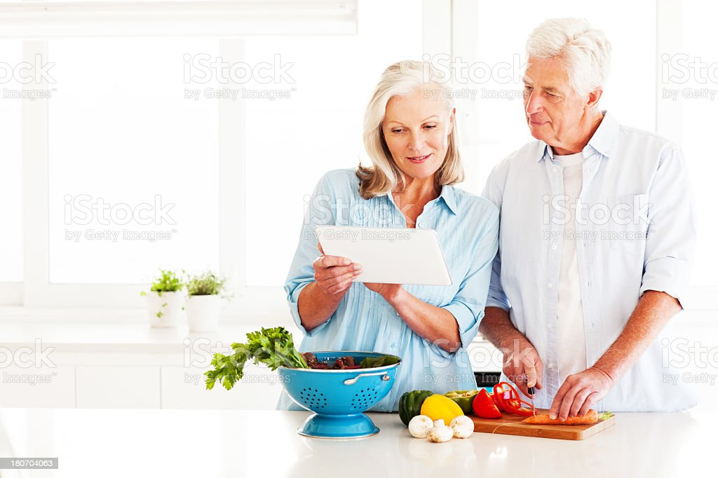 Couple With Digital Tablet Cooking In Kitchen royalty-free stock photo