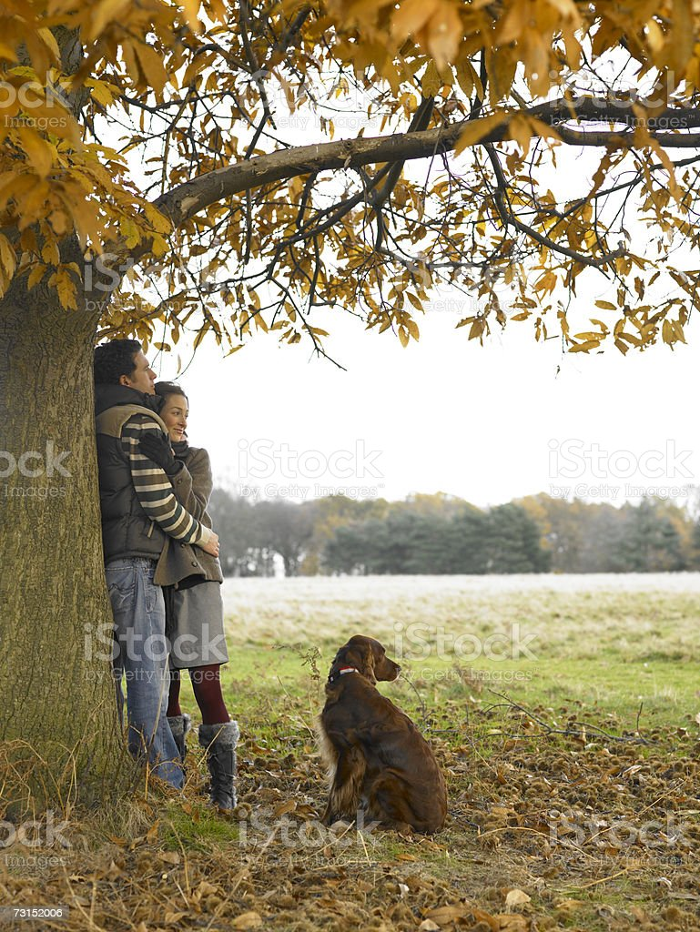 Couple with dog, leaning against tree in park stock photo