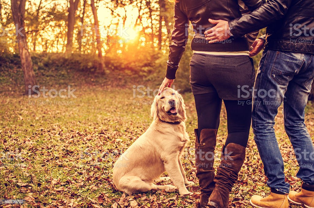Couple with dog outdoors stock photo