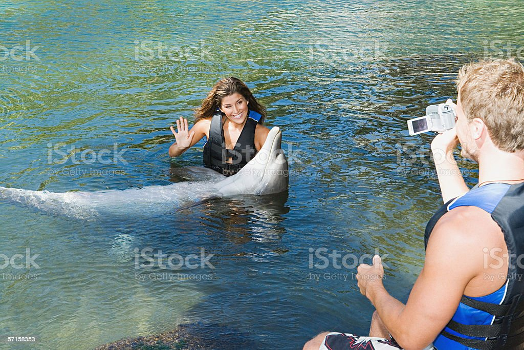 Couple with dolphin stock photo