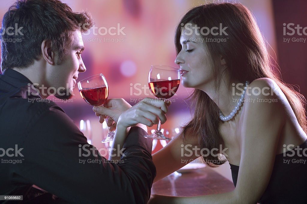 Couple with glasses of red wine in restaurant, celebrating royalty-free stock photo
