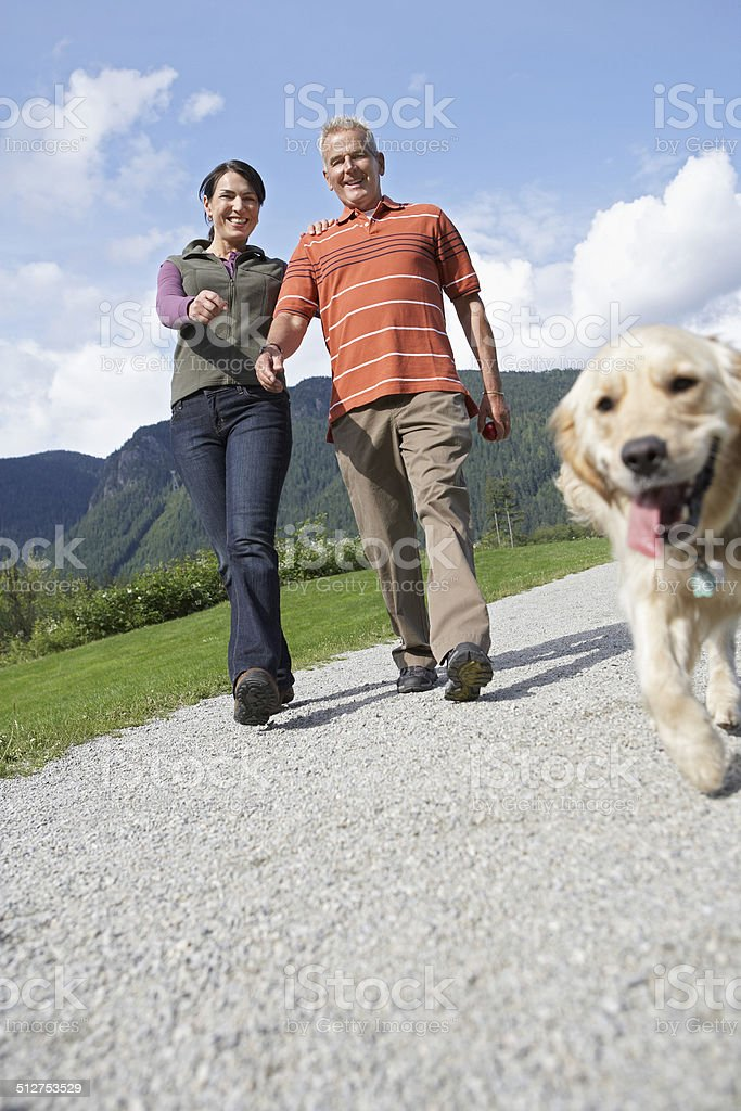 Couple With Golden Retriever On Country Road stock photo
