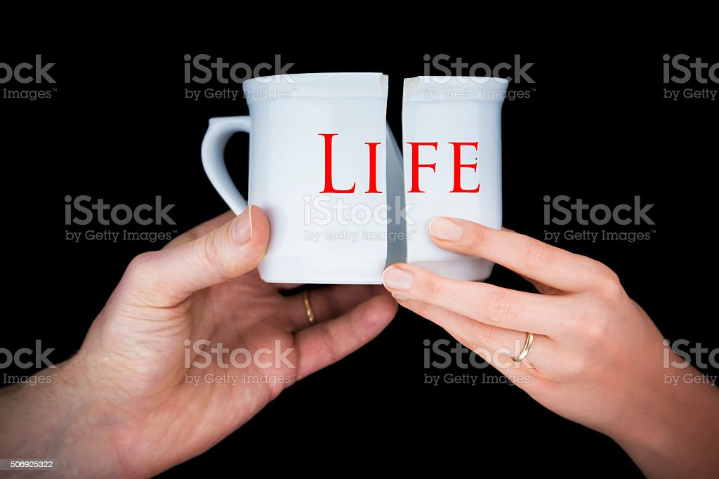 Couple with golden rings holding a broken mug entitled life stock photo