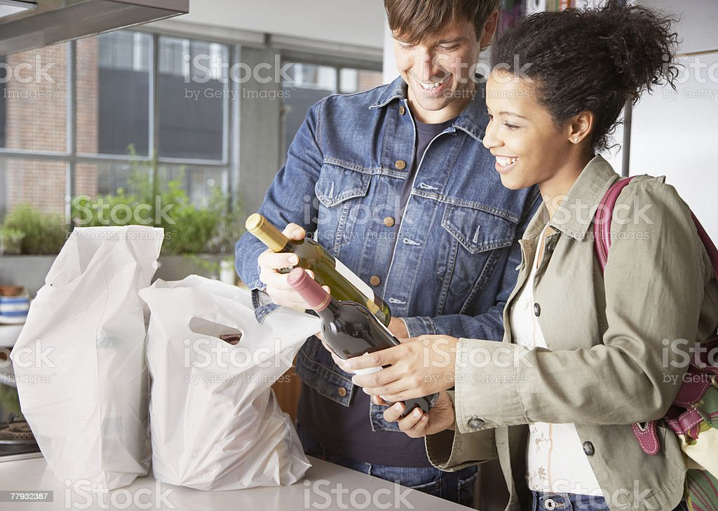 Couple with groceries and wine in kitchen stock photo