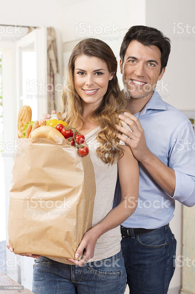 Couple With Grocery Bag In Kitchen royalty-free stock photo