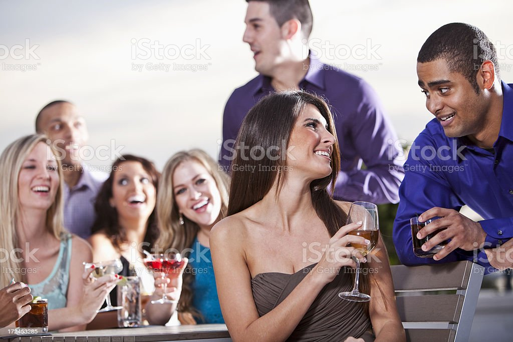 Couple with group of friends drinking at party stock photo