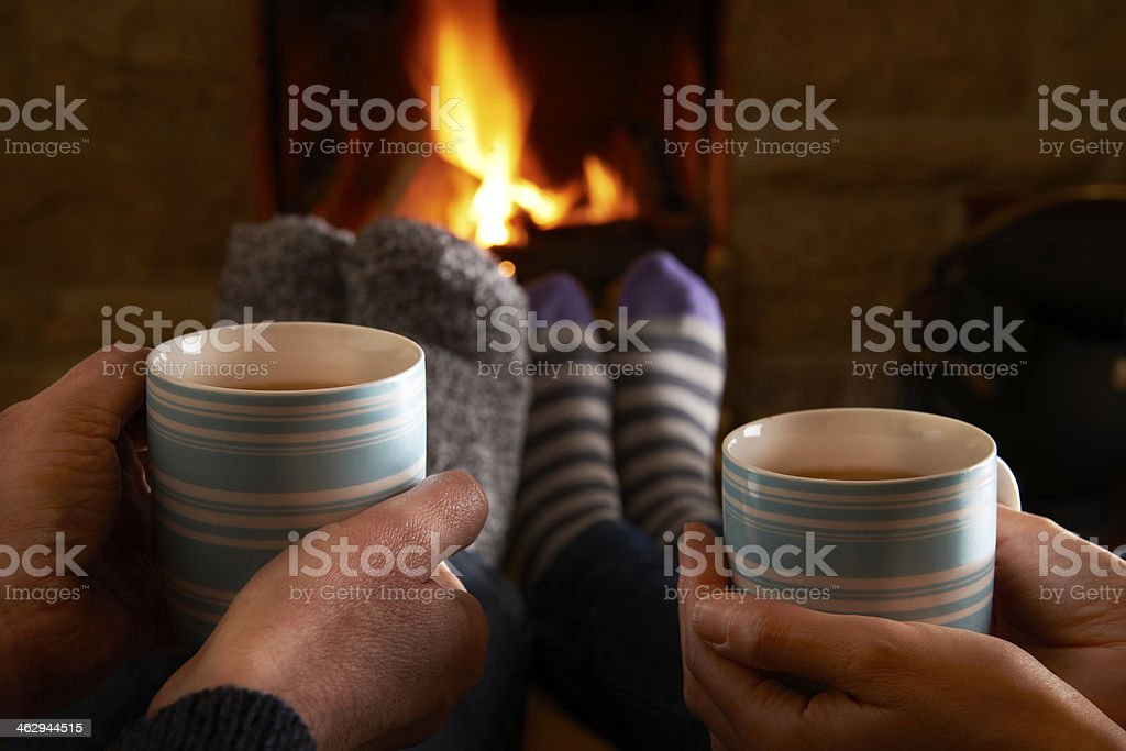 Couple With Hot Drink Relaxing By Fire stock photo