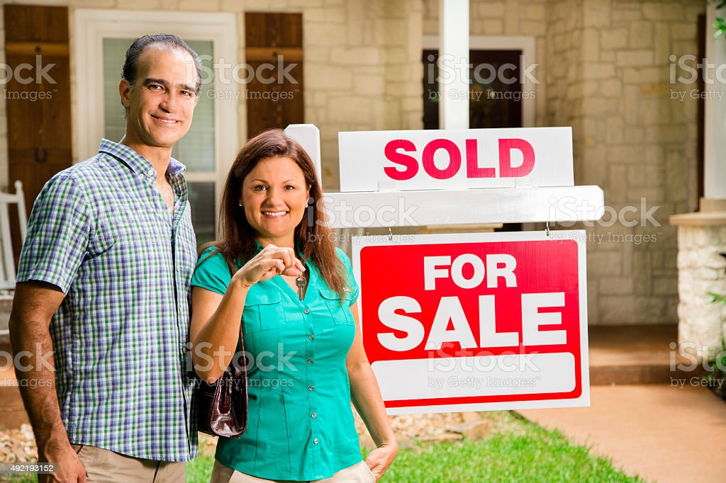 Couple with 'house for sale, sold' real estate sign. Home. stock photo