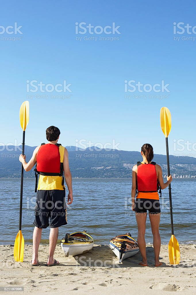 Couple with kayaks stock photo