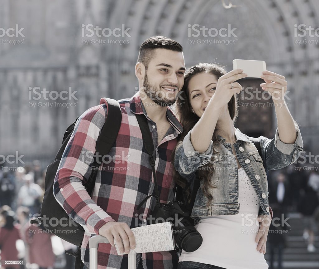Couple with luggage doing selfie stock photo