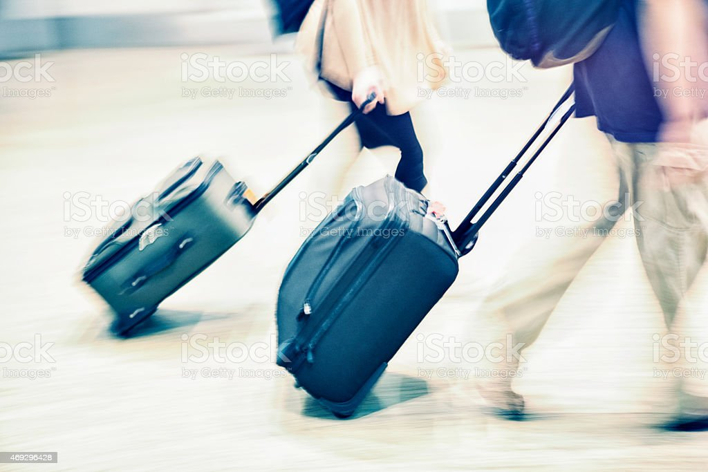 Couple with Luggage in Airport - Blurred Motion Panning stock photo