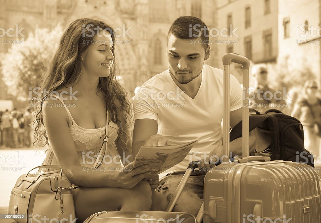 Couple with luggage reading map stock photo