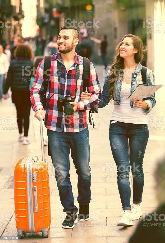 Couple with luggage walking stock photo