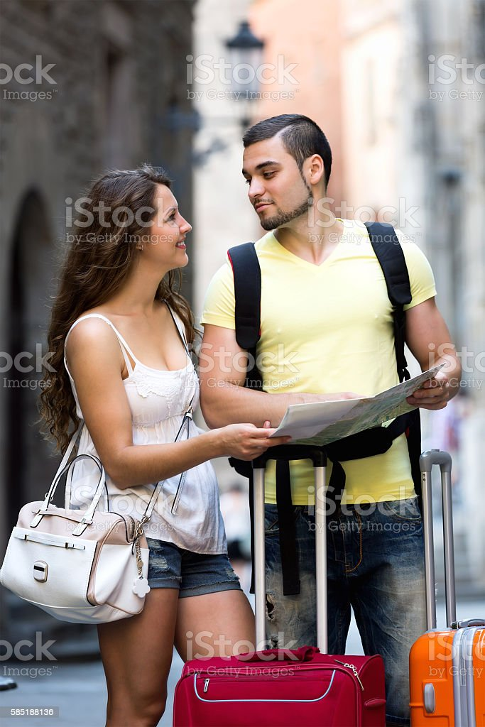 Couple with map on city streets stock photo